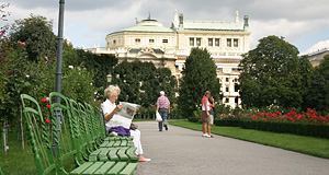 An old lady resting and reading in the Volksgarten with the Burgtheater (Imperial Court Theatre) in the background
